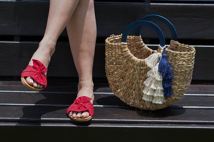Blusa de volantes, sandalias rojas y cartera de mimbre
